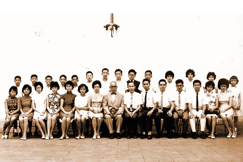 1964年黃國賢校長及教師與14名(佔全港10%)在升中試考獲五年免費獎學金學生合照(趙蘊蘭校長提供)